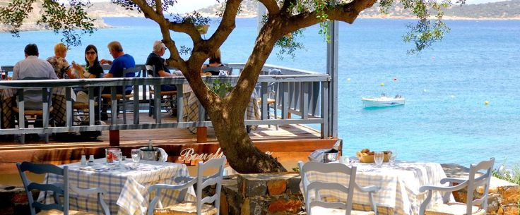 """Terpsis our Cretan Restaurant, a member of """"Chaine des Rotissseurs"""", set in our beautiful gardens on the water's edge with its open air terrace ''floating'' on the Mirabello Gulf, is open every day for lunch."""