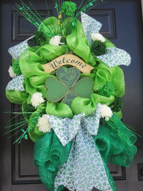 Green, green and more green!! That was my objective for this festive St. Patricks Day deco mesh wreath. There are two types of deco mesh, a pale green foil deco mesh, and a darker green mesh. The darker green mesh was used for an XXL gathering bow at the base of the wreath and the pale green mesh was used on the 24 round metal base wreath. A green four leaf clover Welcome sign is wired to the center of the wreath. 6 Wide white ribbon with embossed glittered shamrocks is added to the…