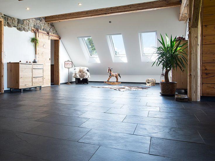 Raum mit anthrazitfarbenem Schieferboden und Holzmöbeln, weisse Wände