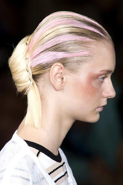 modella di lato con i capelli raccolti e le ciocche rosa