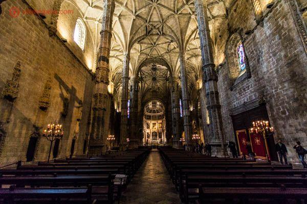 O interior da igreja do Mosteiro dos Jerônimos em Lisboa, com seu interior escuro e seu teto branco e abobadado. Muitos bancos de madeira vão até o altar. A luz entra por algumas janelas em seu topo.
