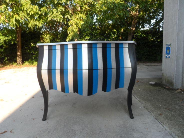 comoncino due cassetti,struttura nera e frontale a righe blu,nere e foglia argento