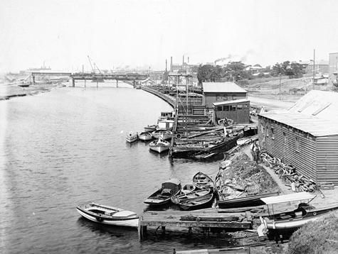 Boatsheds and jetties on the Maribyrnong River, Footscray, 1927. The Hopetoun Bridge, under construction by Victorian Railways, is in the background. The other person Hugh meets is Captain Max. This shows various types of river boats even though it isn't on the Murray river.