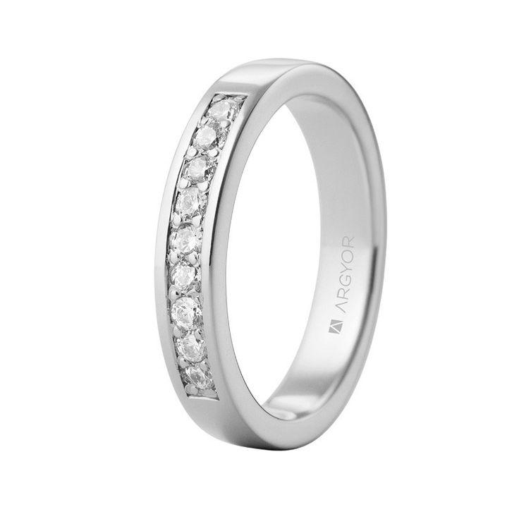 Anillo de diamantes de oro blanco de 18 quilates con 9 diamantes con un total de 0.20ct, engastados en carril con granetes y de talla brillante color H, pureza SI. Una joya de oro y diamantes perfecta como regalo de aniversario, anillo de compromiso o alianza de boda. Referencia 74B0057