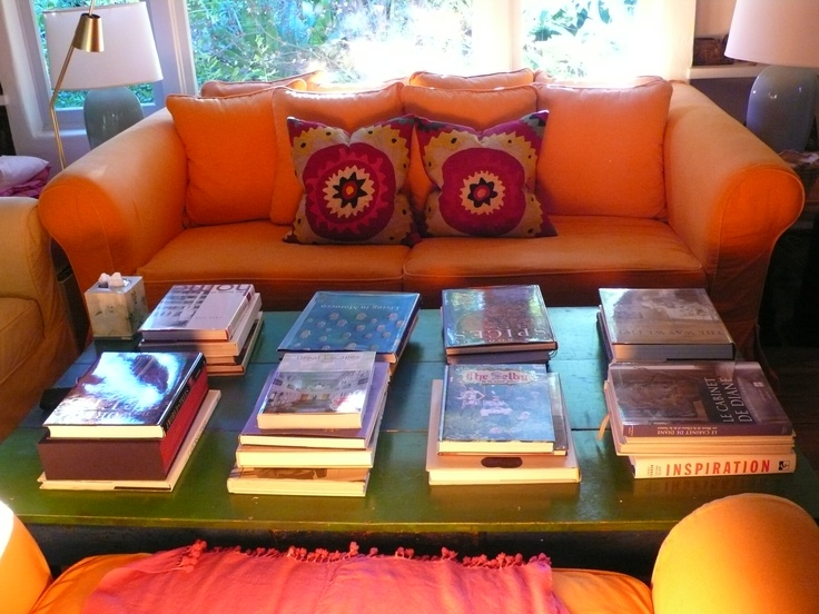 A table in my house with a few piles of books.