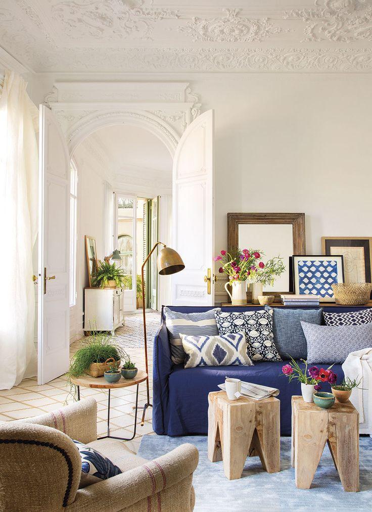 Salón con un sofá azul y dos pequeñas mesas auxiliares de madera