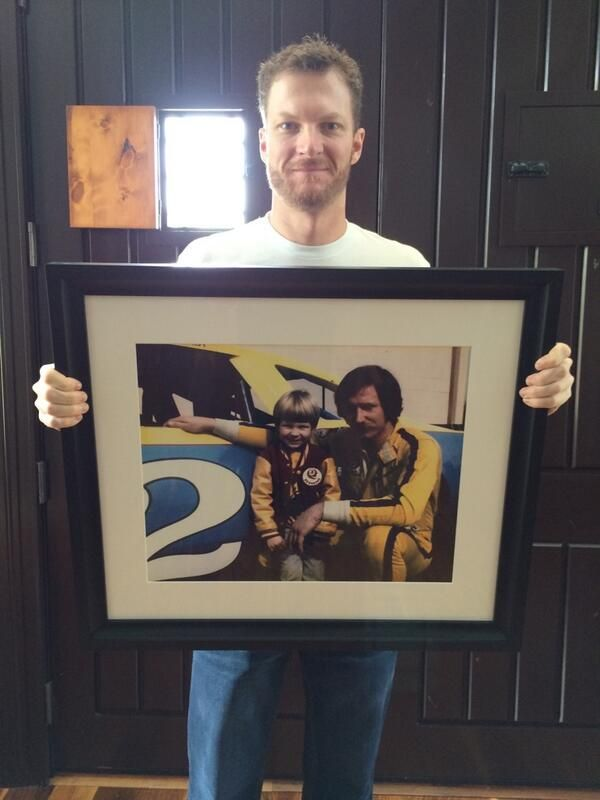 Dale Earnhardt Jr holding a picture of himself with his father Dale Earnhardt Sr.