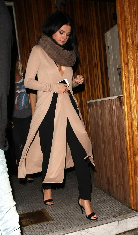 Selena Gomez wears a streamlined cardigan coat, black strappy heels, and a cozy snood scarf