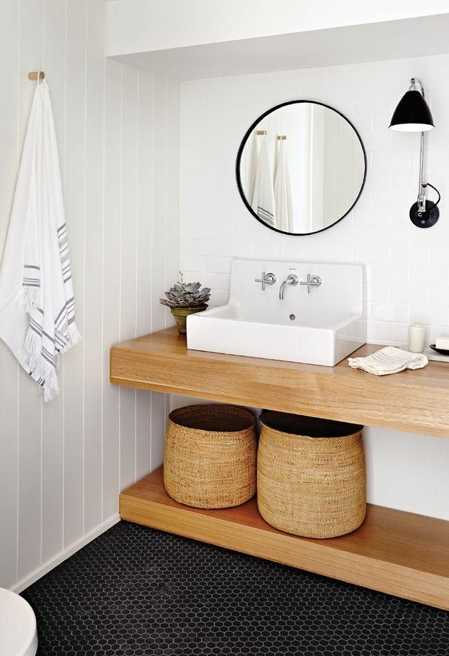 Love this contemporary and minimalist organic modern bathroom with open wood shelving, woven sea grass storage baskets, square porcelain basin sink, black and silver wall mounted sconces, black framed round vanity mirror, gray and white Turkish fouta towels hanging on pegs, and white painted shiplap walls.
