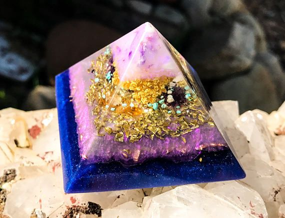 A Violet Flame Orgone Pyramid inspired by the protective and strengthening energy of Father Sky. This powerful orgone crystal pyramid with Shungite, cleanses your EMF and stimulates your connection to the radiant energy of the Sky. A powerful meditation or Feng Shui tool, this Violet Flame Orgone Pyramid balances your energetic environment and offers the blessings of Spring to your space. The tip of this orgone pyramid holds dried flowers and a reflective mica with graphite. Dried yarrow…