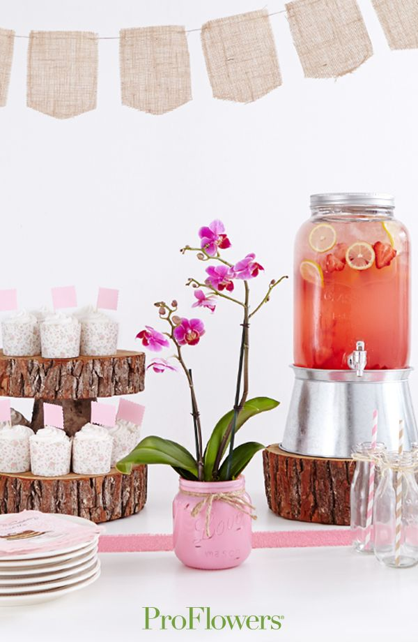 Mason jars and a natural wood cupcake stand help create a rustic party atmosphere.