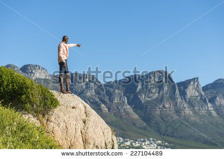http://www.shutterstock.com/pic-227104489/stock-photo-african-black-man-standing-on-a-high-rock-overlooking-cape-town-as-he-points-and-scouts-the-blue.html?src=WuffEuvvGWj02MQSGcnIHQ-1-7 African Black Man, Standing On A High Rock Overlooking Cape Town As He Points And Scouts The Blue Sky, Ocean And Mountains On A Sunny Summers Day Stock Photo 227104489 : Shutterstock