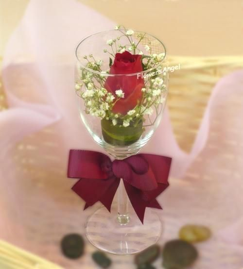 Flower arrange in wine glass single red rose and baby
