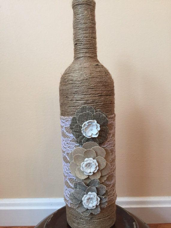 Handcrafted burlap twine wine bottle vase. Lacey accent with flowers. Very pretty white flowers in the middle. Great piece to add to your home decor. Message me about discounts on bulk ordering