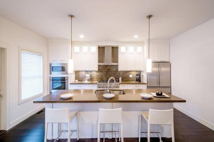 Cuisine transitionnelle avec portes shaker blanches. Ilot central blanc. Comptoir sobre en granit avec dosseret en céramique lustré assorti.