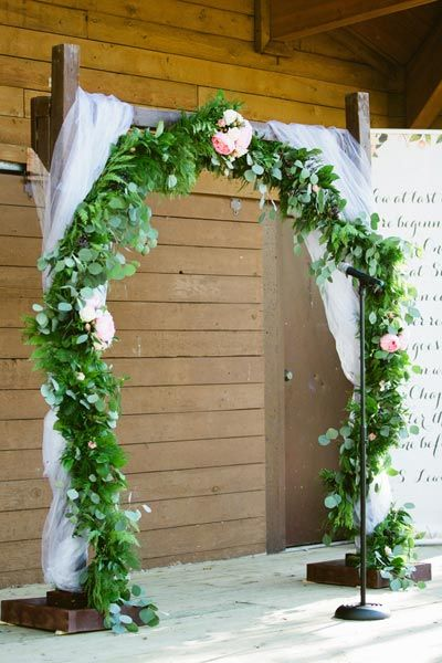 A pretty garland and sheer fabric transform this industrial arch into a fairy tale-worthy setup.