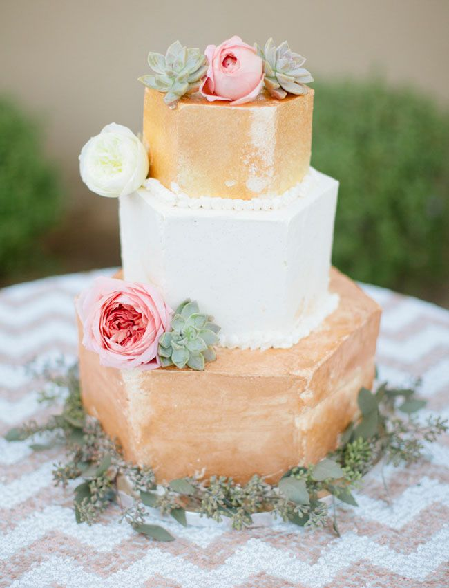 gold cake with pink roses and succulents