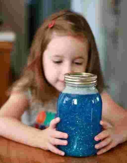 fille qui regarde un bocal rempli de paillettes colorées