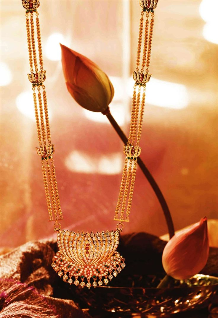 An exquisite lotus necklace in gold by Tanishq with diamonds, rubies, emeralds and pearls.