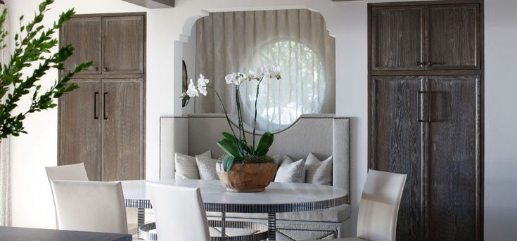 Rustic modern breakfast nook with muted cabinetry, custom upholstery and a touch of orchid. Soft light through the linen draperies over the circular window.