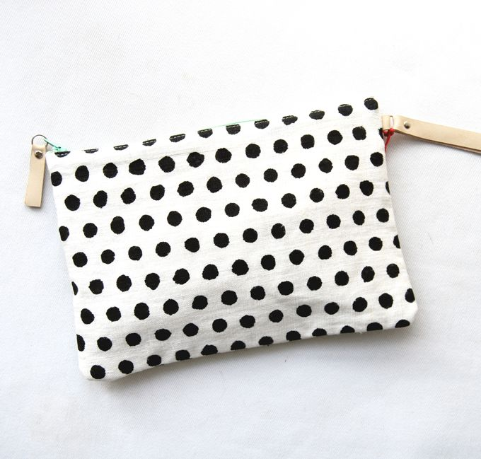 Bolso de mano con estampado de lunares. Con asa de cuero color natural de 15 cm. para poder llevarlo cómodamente.Color: blanco y negro.Composición exterior: 100 % lino.Composición interior: 100% algodón.Medidas: 25 x 17 cm (ancho x alto).