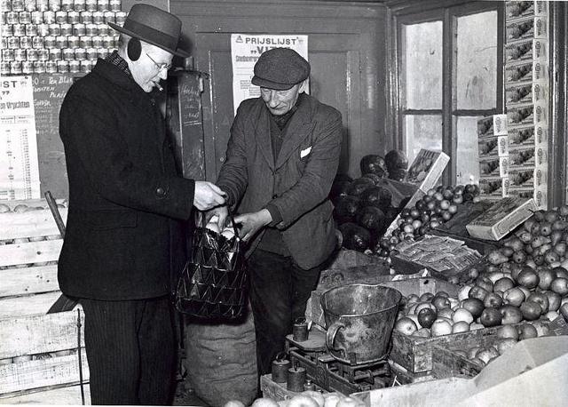 Nederlands: De groentenboer, die ook diepvries en conserven verkoopt, doet appels in de tas van de klant met oorwarmers, Hengelo 1947.  English: Greengrocer. The Netherlands, Hengelo, 1947.