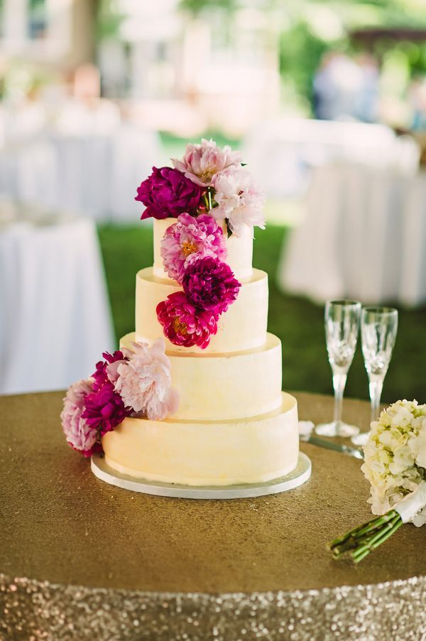 The father of the bride baked the four-tiered cake, which was adorned with a cascade of fluffy peonies in different shades of pink. | Photo by Crystal Stokes