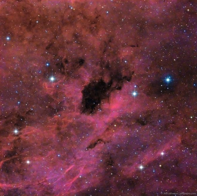 """Thick blankets of dust surround the predominantly dark region in Barnard 343, a dark nebula in the constellation Cygnus. Astrophotographer Jeffrey O. Johnson took this image from his backyard in Las Cruces, New Mexico. """"I took this image after I found the dark area when looking at a star map and looking specifically for dark nebulae. I thought it was fascinating, though I never saw a clear image of it, so I decided to image it myself,"""" Johnson wrote."""