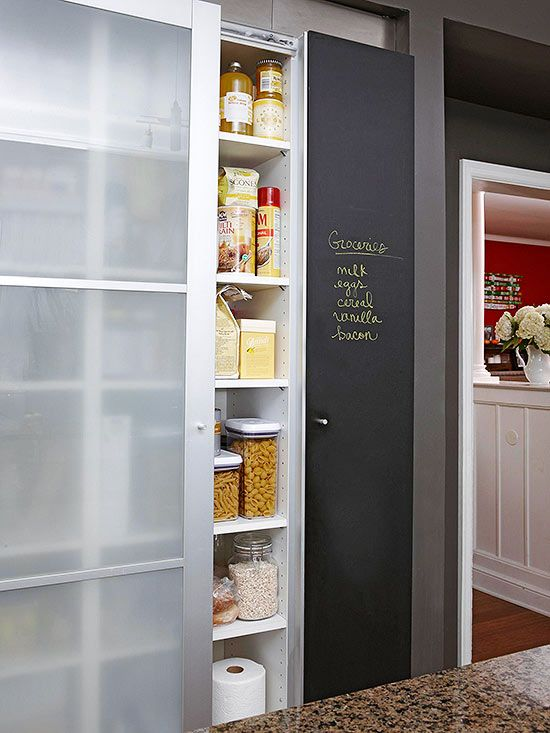 A repurposed closet is transformed into a pantry in this DIY kitchen. The pantry doors slide open for easy access to the storage space. Rows of deep shelves, covered with clouded glass doors, provide plentiful storage for food as well as kitchen essentials like a microwave or even a garbage can. Custom cabinets on both sides of the pantry sport chalkboards made by covering the panels with insets of black laminate./