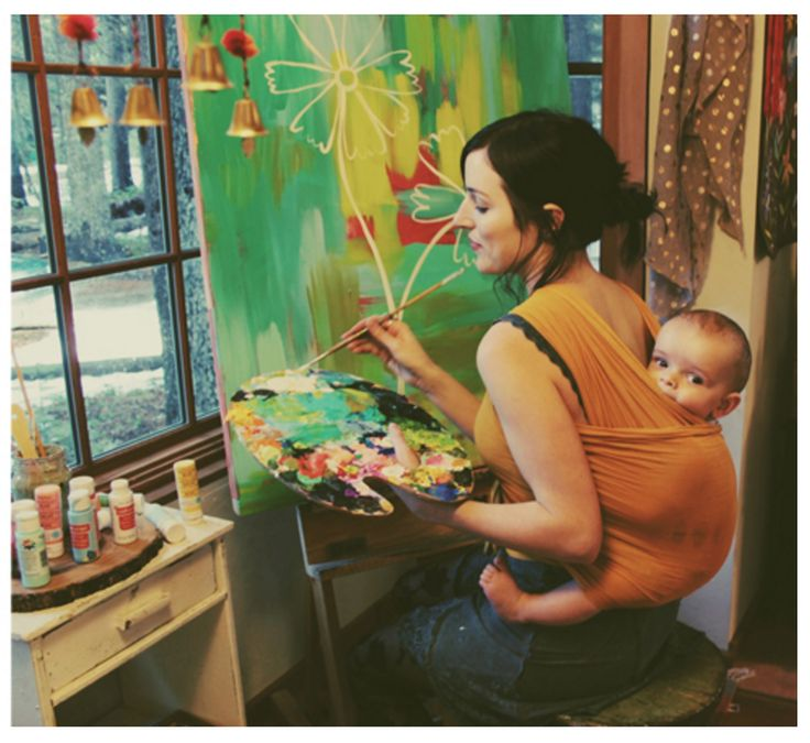 Artist Katie Daisy with baby on back painting.