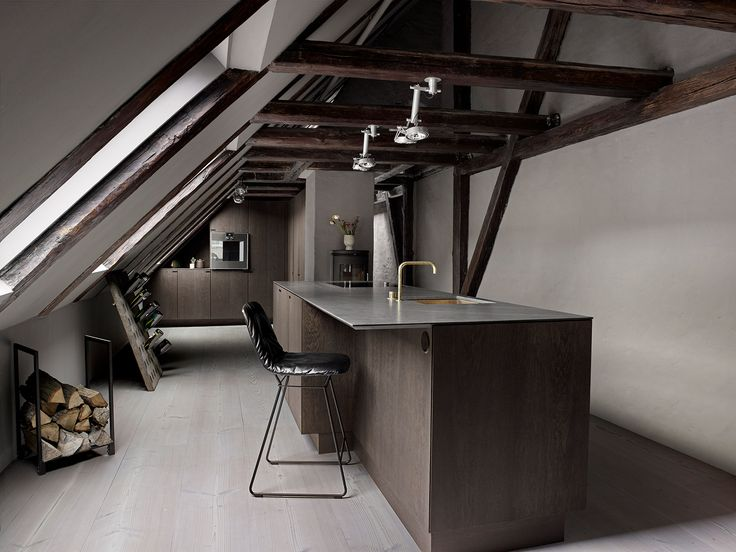 A spacious kitchen balanced between dark and light – set up in a rooftop loft overlooking The Marble Church dome, Copenhagen.