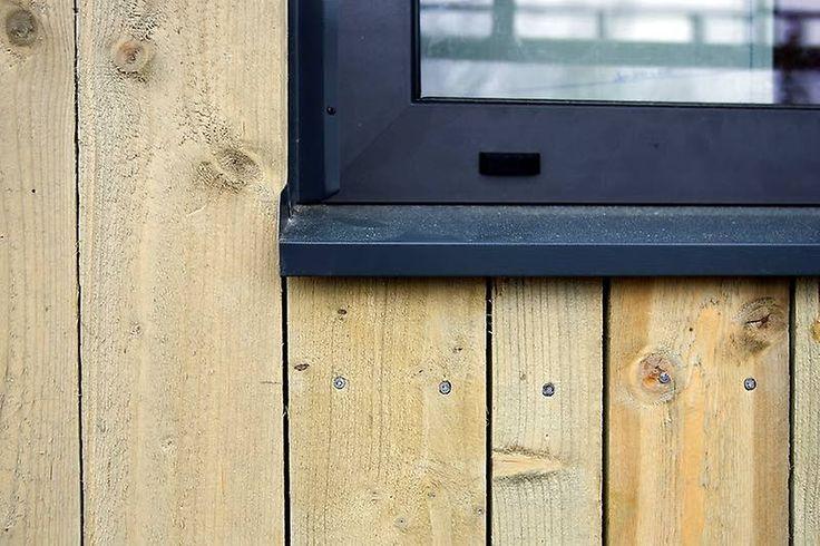 Fasaden är gjord som omvänd lockläktspanel där brädorna har olika bredder för att stämma under fönster, vid dörrarna och knutarna.