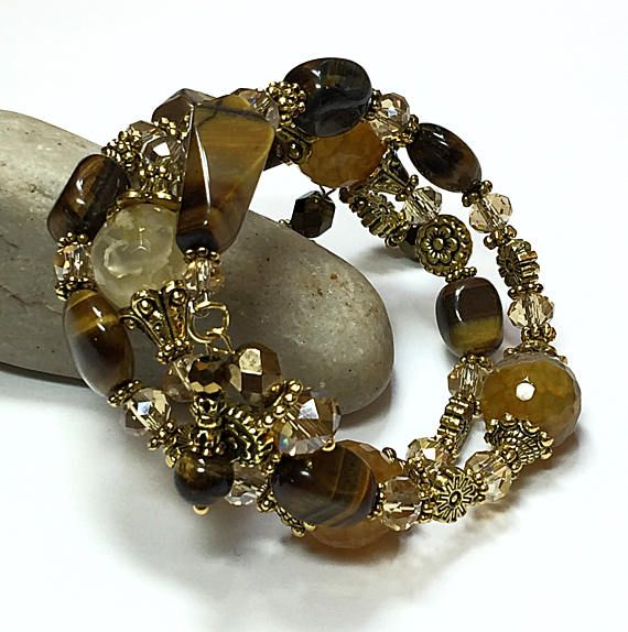 Think of the ensembles you can create with this tigers eye bracelet. This beaded multi warp bracelet is made with natural Tigers Eye beads, amber faceted beads and crystal faceted beads. These beads are paired well with Bali-styled gold spacer beads and bead caps. This memory wire