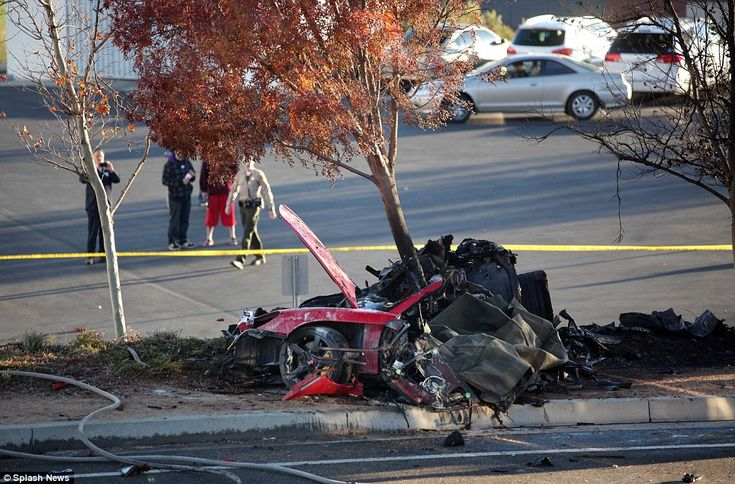 Tragic: A sheet covers part of the wreckage in which actor Paul Walker died after the car went up in flames in Santa Clarita- actually it covers what is left of their bodies