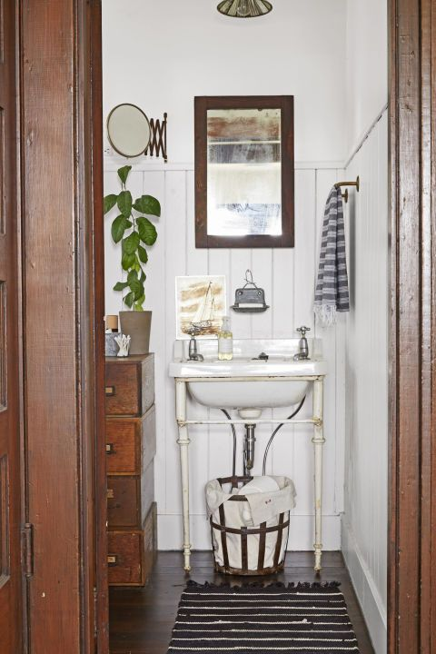 """The couple made the home's lone bathroom feel airier by ripping out the existing vanity and replacing it with an antique wall-mounted sink with cast-iron legs. An old metal basket lined with linen houses extra rolls of toilet paper. The chest of drawers wasn't actually part of an estate sale Lindsea and Danny were shopping, but that didn't stop them from making an offer. """"We loved it, and now it's where we keep all of our toiletries,"""" says Lindsea."""