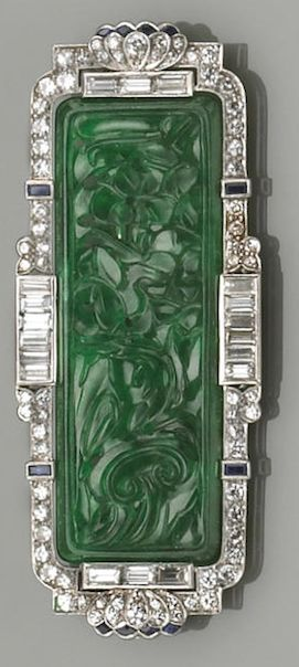 An art deco, jadeite jade, diamond, sapphire, and platinum brooch pendant, circa 1925 centering a rectangular-shaped plaque with floral carving, framed by baguette and transitional round brilliant-cut diamonds, sapphire detail; estimated total diamond weight: 2.85cts.; length: 2 7/16in.