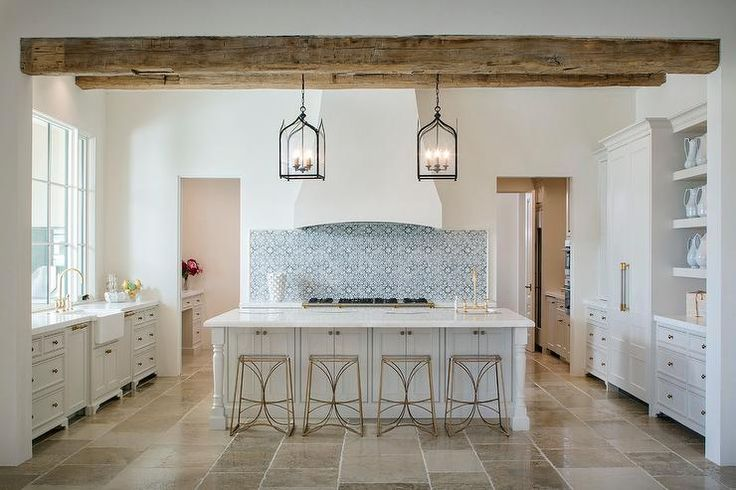 Mediterranean kitchen features a white stucco vent hood which stands over a white and blue mosaic tiled backsplash and a stainless steel stove.