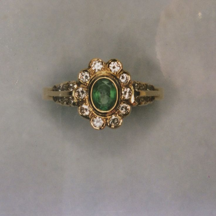 Emerald and diamond cluster ring in yellow gold with finely detailed shoulders inset with small diamonds