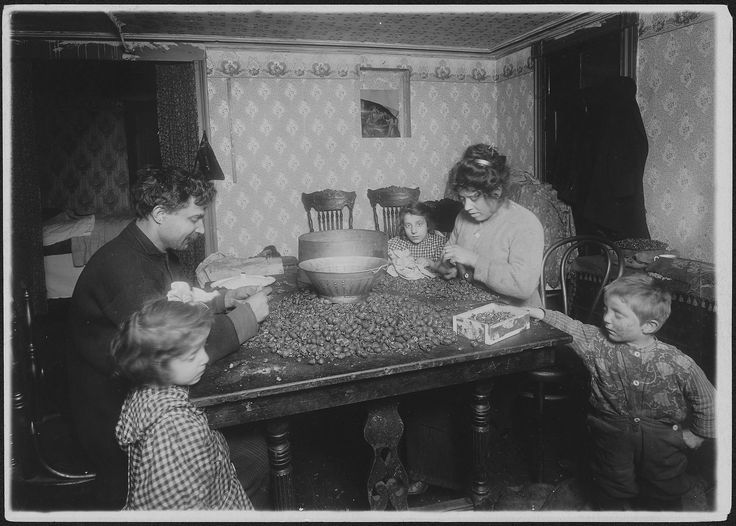 Picking nuts in dirty basement. The dirtiest imaginable children were pawing over the nuts eating lunch on the tabel, etc. Mother had a cold and blew her nose frequently (without washing her hands) and the dirty handkerchiefs reposed comfortably on table close to the nuts and nut meats. The father picks now. New York City, December 1911   Photographer: Louis Wickes Hines (pinned by haw-creek.com)