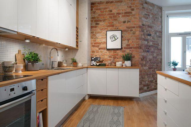 Biała kuchnia ze ścianą z czerwonej cegły i deskami z drewna na podłodze