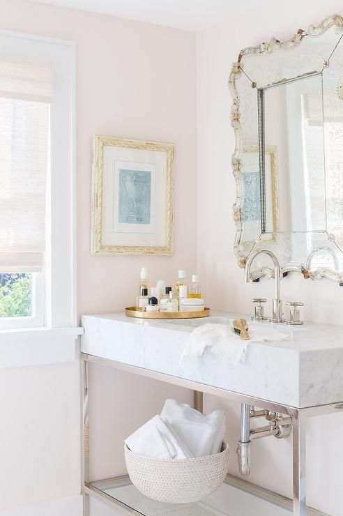 Alyssa Rosenheck - Raquel Garcia Design - Lovely pale pink bathroom boasts an ornate vanity mirror hung above a nickel and marble washstand finished with a polished nickel gooseneck faucet. The vanity is topped with a round gold tray as a window is covered in a white linen roman shade.