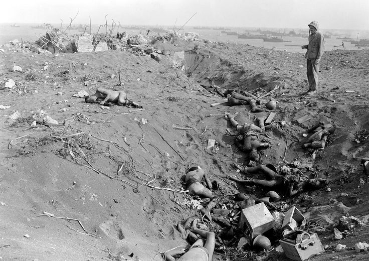 A U.S. Marine views dead Japanese soldiers that were blasted out of a pillbox on Iwo Jima, on March 3, 1945.