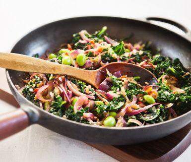 Prova fräst grönkål med ingefära, vitlök och edamamebönor som ett fräscht tillbehör till skinka och revbensspjäll. Den frästa grönkålen är kryddad med chili, vitlök och ingefära vilket ger den ett asiatiskt sting. Ett lätt och nytt alternativ till långkål, stuvad grönkål eller halländsk grönkål.