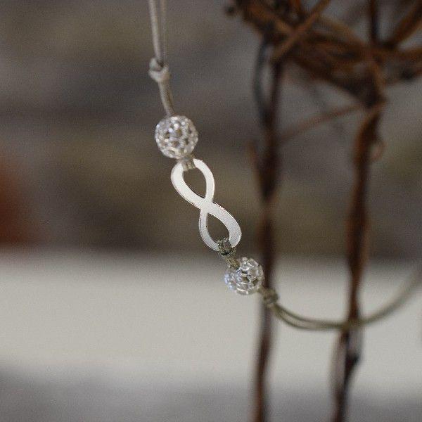 NEKONEČNO-Náhrdelník vyroben z pevné hedvádné šnůrky, nastavitelné délky,navlékání přes hlavu, zakončem stříbrnými perlami a medailonkem ve tvaru stopy Impronte. Ozdoben stříbrným komponenten ve tvaru ležaté osmičky a stříbrnými perlami.