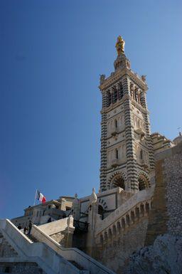 Arrivée devant la basilique La Basilique Notre Dame de la Garde, aussi appelée la Bonne Mère par les Marseillais, est la gardienne et la protectrice de la cité phocéenne. Symbole emblématique de Marseille, elle est mondialement connue, un peu comme la statue du Christ pour Rio de Janeiro ou le célèbre panneau Hollywood. Quand on voit la Bonne Mère, on sait que l'on est à Marseille !