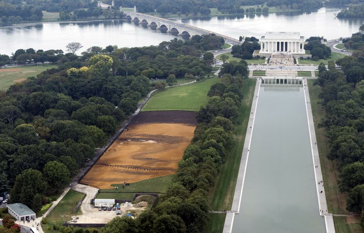 "The landscape portrait, ""Out of Many, One"" by Cuban American artist Jorge Rodriguez-Gerada, appears on the National Mall in Washington, D.C., Oct. 1, 2014. The 6-acre portrait, midway between the World War II Memorial and the Lincoln Memorial, used approximately 2,000 tons of sand, 800 tons of soil, 10,000 wooden pegs, miles of string and assistance from GPS topography poles, which allows the materials to be placed with precision. It will be viewable until October 31."