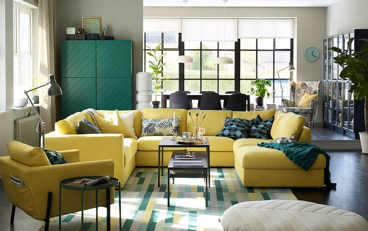 Large u-shaped yellow sofa in the center of an open plan living and dining room.