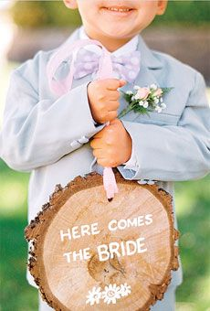 "Have your ring bearer carry your bands on something unique: a felt flower, a mini fishing rod, or a slice of wood that says ""Here Comes the Bride."""