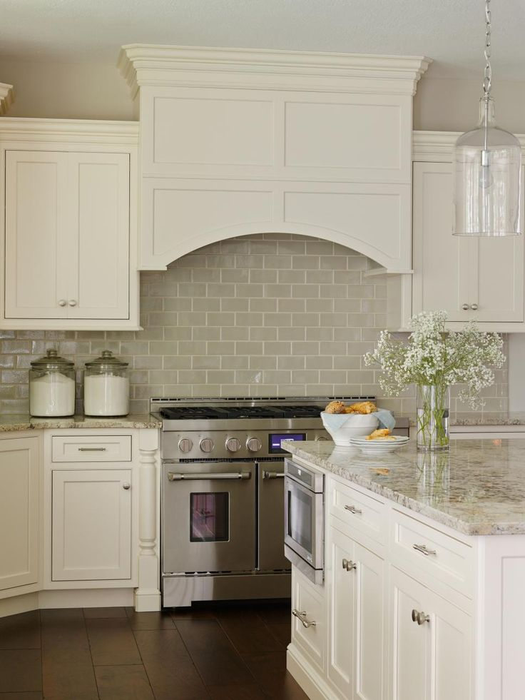 Off-white cabinetry paired with a glossy neutral tile backsplash grounds this kitchen in a soft, serene color palette. Custom cabinetry features inset doors, a built-in range hood and decorative moldings that mimic the room's freestanding furniture.