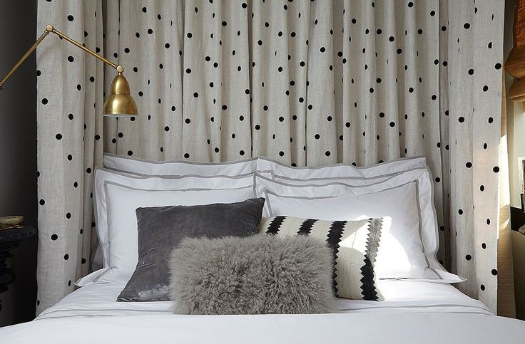 """A half-canopy bed made of three drapes hung floor-to-ceiling (one behind the bed, two alongside) rather than dressing up the bed with curtains all around gives the room """"a more airy appearance"""" in the bedroom and """"also helps make the ceiling appear higher than it is."""""""